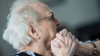 elderly person in a care home clasping hands
