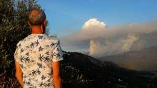 Човек посматра облак дима који је настао услед пожара на планини Сијера Бормеха