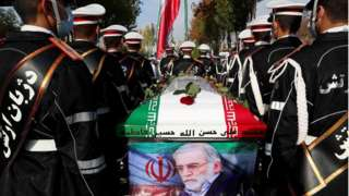 Militares de costas carregam caixão com bandeira do Irã, em área externa com dia ensolarado
