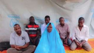 A still taken from a video showing a kidnapped aid workers, and five men believed to be her colleagues. They are all sitting on mats in front of tarpaulin.
