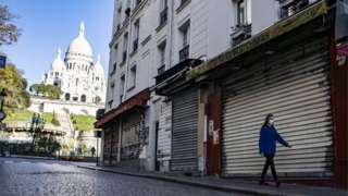 A woman walks on an empty street in Paris