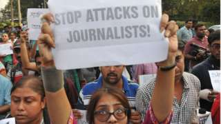 "A journalist in India holds a sign reading ""Stop attacks on journalists"" at a protest in Kolkata, 2017"