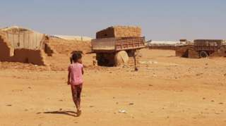 A little girl walks near makeshift shelters at Rukban camp, on the Syria-Jordan border (27 September 2018)