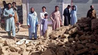 Residents gather near the rubble of a damaged house following an earthquake in Harnai, Balochistan, Pakistan, on 7 October 2021