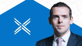 Leader Douglas Ross in front of Scottish Conservative logo