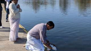 Radhika Kadaba's father's ashes being placed into the river
