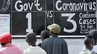 People reading a blackboard news board in Monrovia, Liberia - Monday 30 March 2020