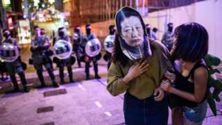 A woman wears a face mask depicting Secretary for Justice Teresa Cheng as she poses for photos in front of a line of riot police as they stand in a line to block entry to the Lan Kwai Fong area during Halloween in Hong Kong on October 31, 2019