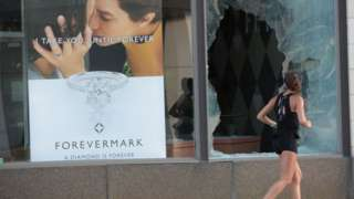 A jogger runs past a broken Chicago storefront window after parts of the city had widespread looting and vandalism, on August 10