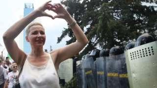 Maria Kolesnikova haciendo un signo de corazón con sus manos frente a un grupo de policías antidisturbios en Minsk.