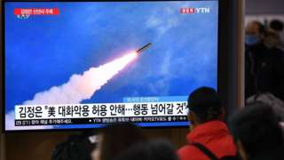 People watch a television news programme showing file footage of North Korea's missile test,