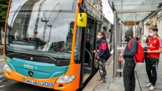 Passengers in masks getting on a bus in Cardiff