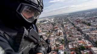 A policeman is seen on board a helicopter as it flies over Mexico City in 2018