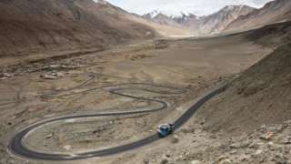 Workers ride on the back of a truck along Pangong Lake road in northern India's Ladakh region