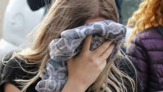 The teenager covers her face as she arrives at court
