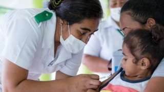 A nurse in Samoa gives a vaccine to a young girl