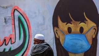 Palestinian man walking past mural in Gaza Strip.