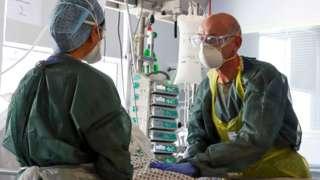 Equipe médica usando EPI completo no Frimley Park Hospital em maio de 2020