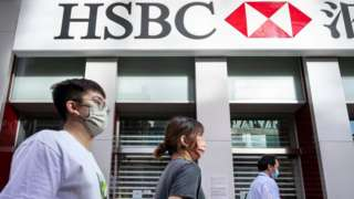 Pedestrians walk past the British multinational banking and financial services holding company, HSBC in Hong Kong.