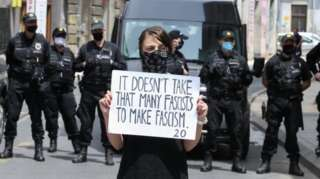"A protester in front of police in Sarajevo holds a placard that reads: ""It doesn't take that many fascists to make fascism"". Photo: 16 May 2020"