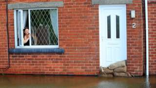 Woman looking out a window of a house, which is surrounded by floodwater