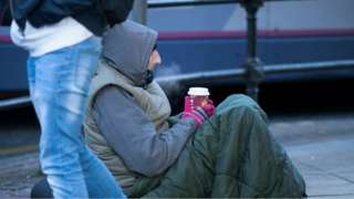 Homeless man with a hot drink in the cold weather