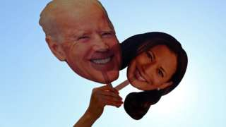 A supporter holds up cutouts of Joe Biden and Kamala Harris near the White House after media announced that Democratic U.S. presidential nominee Joe Biden has won the 2020 U.S. presidential election, in Washington D.C., U.S., November 7, 2020.