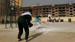 Afghan girls play cricket on the school grounds in Kabul on December 28, 2010