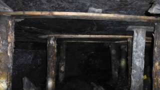 """A photo from inside the mine showing """"pallet"""" wood holding up the ceiling"""