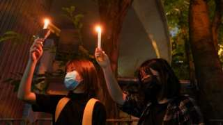 Two women hold candles near Victoria Park, June 2021