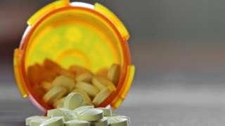 White pills in a plastic bottle