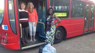 Landlady Eunice and two members of the fundraising committee stand with the bus