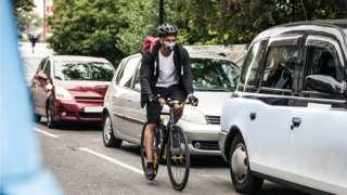 Man cycling past cars