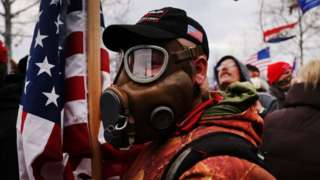 Trump supporter seen in a gas mask holding a US flag