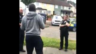 Two white police officers speaking to a black man