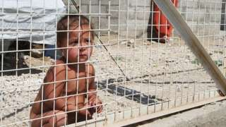 Child crouching behind a metal fence