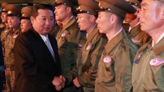 North Korea's leader Kim Jong Un greets military personnel at the Defence Development Exhibition, in Pyongyang, North Korea, in this undated photo released on 12 October 2021