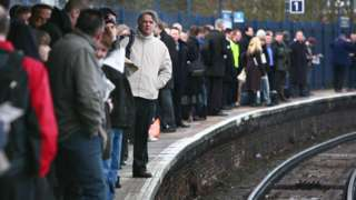 Commuters wait on a railway platform