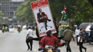 Supporters of President Uhuru Kenyatta hold a banner bearing a picture of Kenyatta as they celebrate on November 20, 2017 in Nairobi after Kenya's Supreme Court dismissed two petitions to overturn the country's October 26 presidential election re-run, validating the poll victory of Kenyatta