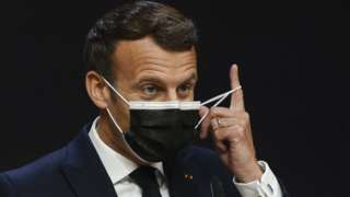France's President Emmanuel Macron takes off his facemask before giving a press conference during the European Social Summit hosted by the Portuguese presidency of the Council of the European Union at the Palacio de Cristal in Porto on May 8, 2021
