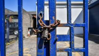 File image of a rusty chain and padlock securing blue painted steel gates to prevent access to a business on a trading estate in Bristol