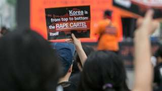 Feminists chant slogans as they hold signs that read, 'Korea is from top to bottom the Rape Cartel itself', during a rally on July 27, 2019 in Seoul, South Korea.