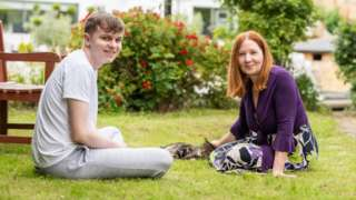 Benjy e Anne Fish sorriem sentados no gramado