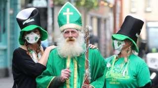 St Patrick beside two women wearing masks with shamrocks