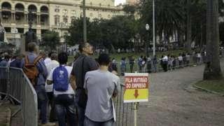 Pessoas aguardam numa enorme fila de um mutirão de emprego