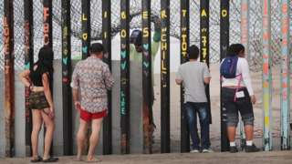People on the Mexican side watch as workers in the US repair the border
