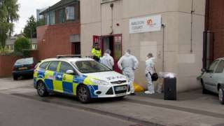 Police vehicle and forensic officers at a block of flats