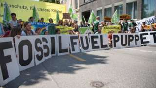 """Activists of Greenpeace protest with a sign reading """"fossil fuel puppet"""" in front of the US embassy in Bern, 2 June"""