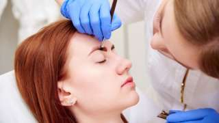Beautician working on a woman's eyebrows