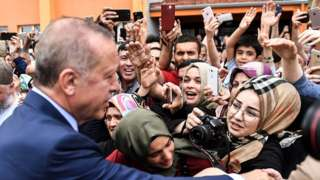 President Recep Tayyip Erdogan, leader of the Justice and Development Party (AKP), is greeted by supporters as he leave the polling station after casting his vote